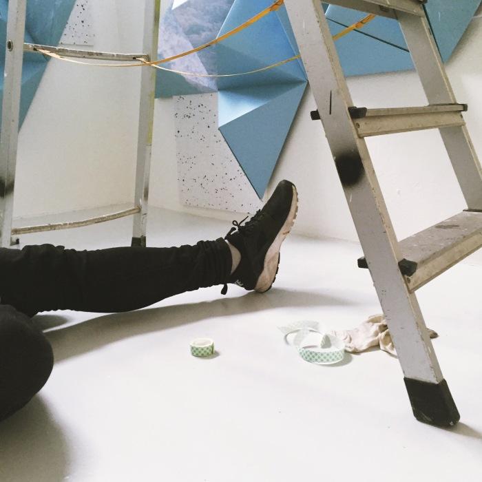Stine Raastad tar en pust i bakken under montering av et fotografisk verk som går i dialog med rommets arkitektur.